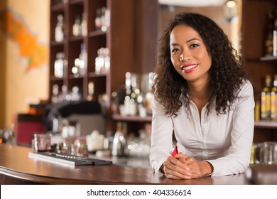 Asian female bar owner standing behind counter and smiling at camera