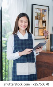 Asian female barista wear blue apron hold tablet computer coffee menu with smiling face in cafe waiting order from customer ,Coffee business owner concept.