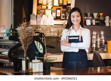 Asian female barista wear jean apron crossed her arms at counter bar with smile face, cafe service concept, owner business start up.