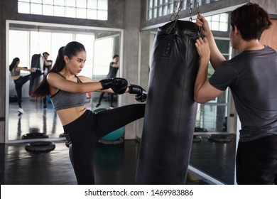 Asian Female boxer kick punching bag held by personal trainer at fitness gym. Athletic girl train Thai boxing punch and kick with coach for bodybuilding and healthy lifestyle concept.