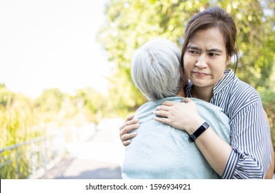 Asian female caregiver and senior patient with depression,alzheimer disease,hugging,needs love,attention closely,facial expression,feel bored,disgusted to pretend to show love to the elderly woman