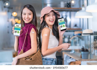 Asiatische weibliche freundlich lächelnde Teenager Hand-Gesten zeigen Impfmarke gegen Covid-19 und digitalen Impfpass von Smartphone-Bildschirm, nachdem Impfstoff verhindert Gesundheitskonzept