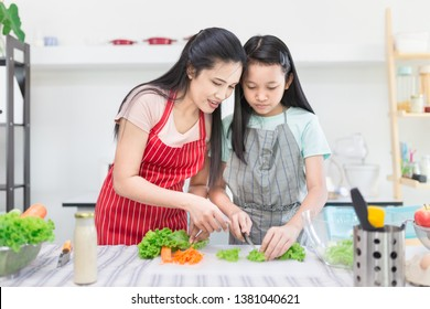 Asian female and asian children cooking organic salad, they use knife cut vegetables on chopping board, children learning to cook in kitchen room, family activity, they feeling happy and smile