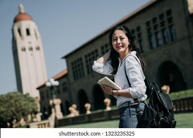 Asian female college student study abroad carrying backpack and school book standing outdoor university on sunny day america. young woman exchange learn language English speaking countries