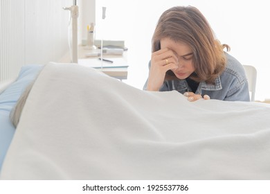 Asian female daughter  crying nearby dead body under whtie clothe on bed in hospital.