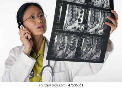 Asian female doctor looking at an MRI scan while talking on a cellphone. Horizontal shot. Isolated on white.