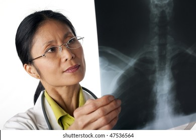 Asian female doctor looking at an x-ray of lungs. Horizontal shot. Isolated on white.