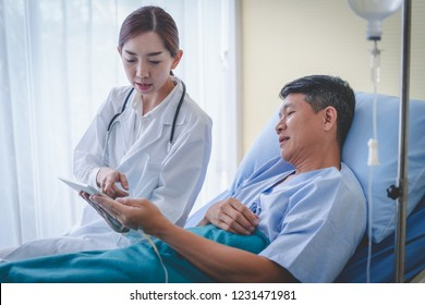 Asian female doctor with male patient is checking the results from the tablet.