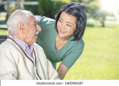 Asian female doctor playing and smiling with mature elderly man in the hospital garden.  Retirement community concept
