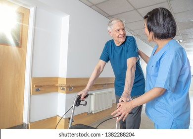 Asian female doctor reassuring mature elderly man with walker. Man and woman smiling happy in the hospital aisle. Retirement community concept.