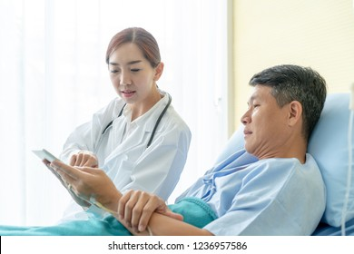 Asian female doctor sitting on hospital bed and discussing with senior patient - selective focus point