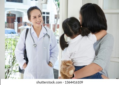 Asian female doctor in uniform standing near the entrance in the house and talking to mother about her little daughter
