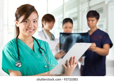 Asian Female doctor wearing a green scrubs and stethoscope. Her Colleges are out of focus in the background.