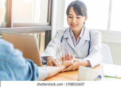 asian female doctor working in hospital office talking to patient, checking blood pressure of patient with two fingers on wrist, documentations of symptoms, health insurance and medical care contract