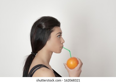 asian  female drinking juice with a straw from an orange