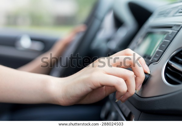 asian female driver touching dashboard in car