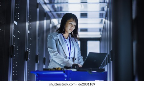 Asian Female IT Engineer Working on a Laptop on Tool Cart, She Scans Hard Drives.  She's in a Big Data Center Full of Rack Servers.