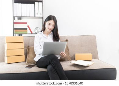 Asian female entrepreneur chat with customer about product information, shopping online market, delivery business office, she pack product box and holding laptop, she sitting on sofa