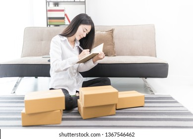 Asian female entrepreneur check order of customer, she write customer information on notebook, shopping online market, delivery business office, she pack product box