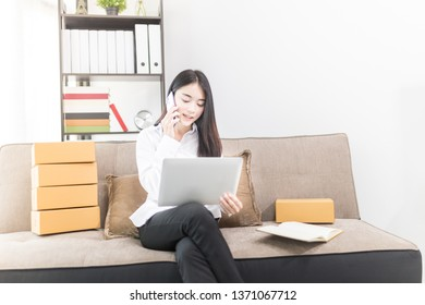 Asian female entrepreneur phone with customer about product information, shopping online market, delivery business office, she pack product box and holding laptop, she sitting on sofa