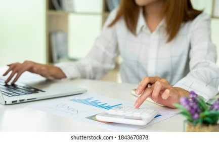The Asian female finance staff is pressing a calculator to check the Company's financial investment results. To summarize and prepare to report the results to the meeting, Concepts of calculation