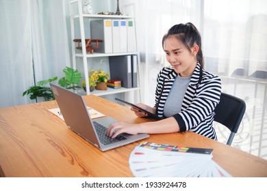Asian female freelance designer using digital tablet computer laptop wireless internet software engineering web design app design technology research panning ideas innovation, on desk workstation