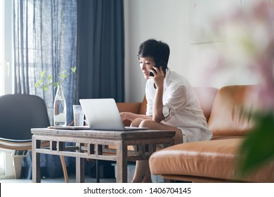 Asian female freelancer talking on smart phone while working at home