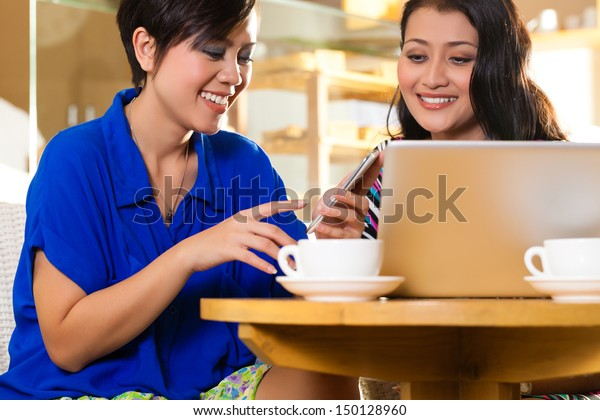 Asian female friends enjoying her leisure time in a cafe, drinking coffee or cappuccino and working on a laptop computer