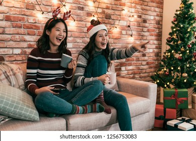 asian female friends watching movie and having fun at Christmas eve sitting on couch with gift boxes under xmas tree. young girls cheerfully point to television screen comedy showing sharing laughing