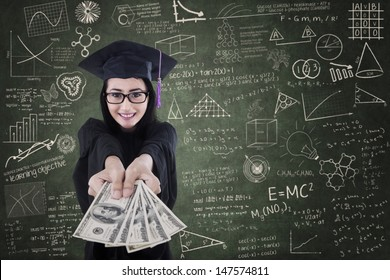 Asian female graduate giving money in classroom - education cost concept