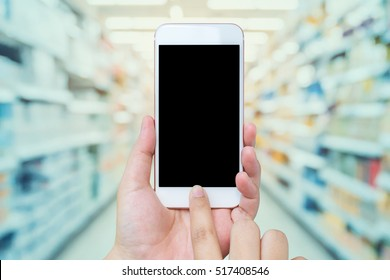 Asian Female hand holding mobile smart phone with Supermarket aisle blur background