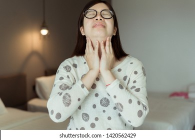 Asian female have a sore throat,Woman touching her neck with hands,Health care Concept