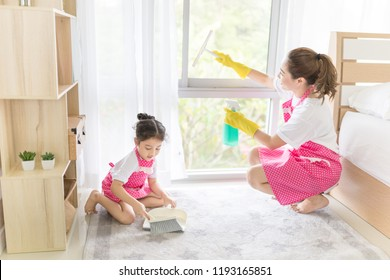 asian female and her daughter clean a room, they feeling happy and fun, family activity