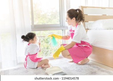 asian female and her daughter clean a room, they wipe glass window,  they feeling happy and fun, family activity