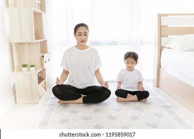 Asian female and her daughter exercise with yoga activity, Asian traditional therapy, meditation training