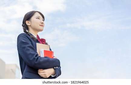 Asian female high school student looking up to sky.