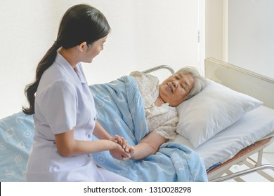 asian female home nursing holding hand of older lady on the bed and encouraging patient
