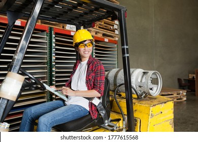 Asian female industrial worker with clipboard looking away while sitting in forklift truck