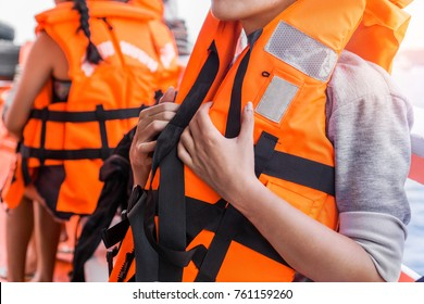 Asian female in life jacket with other people near sea on ship