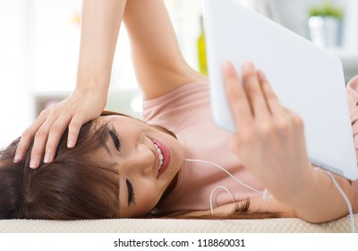 Asian female lying on bed enjoying  music