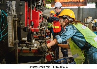 asian female and male manufacturing workers operating steel drilling machine together in line of metal work production factory