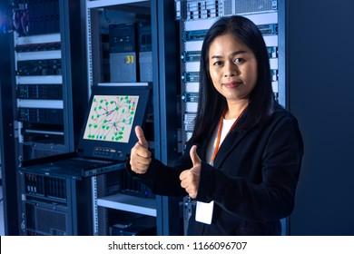 Asian female network administrator show thumb up hands to confirm great work and trustworthy in front of networking and servers rack cabinet in data center room