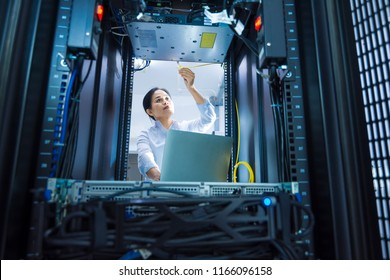 Asian female network administrator working with networking devices installed on rack cabinet in data center room
