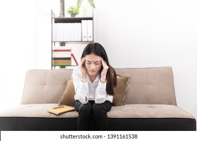 asian female officer dizziness and stress in work time , she feel serious and headache , she use hand catch her head, she sitting on sofa, office syndrome