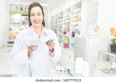 asian female pharmacist explain about how to use drug, she holding drug strip pack with her hand and talk with customer in drugstore