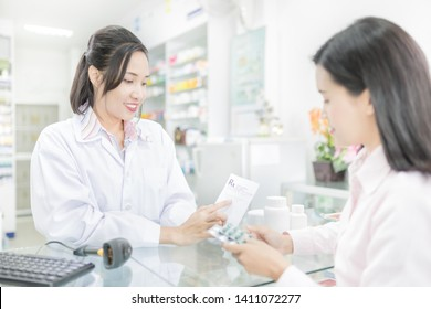 asian female pharmacist explain about how to use drug, she holding prescription with her hand and talk with customer in drugstore, pharmacist send drug to asian patient