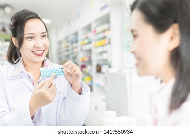 asian female pharmacist explain about how to use contraceptive drug, she holding contraceptive drug strip pack with her hand and talk with customer in drugstore, Oral contraceptive pill
