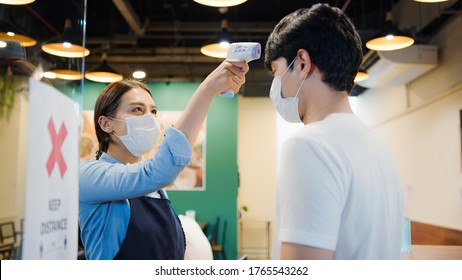 Asian female restaurant staff using infrared thermometer checker or temperature gun on male customer's forehead before enter. Coronavirus Covid-19 precaution fever checking, new normal lifestyle