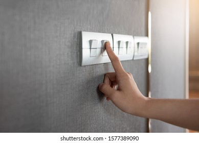 Asian female right hand is turning on or off on grey light switch over gray textile texture wall at the house or hotel. Copy space.