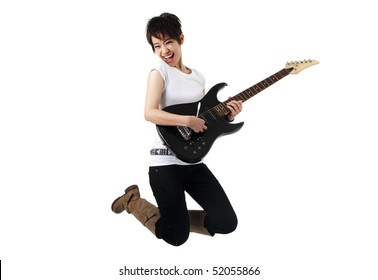 Asian female rockstar holding guitar jumping in air.